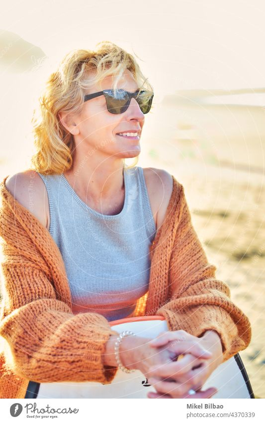 Portrait of a young mature blonde caucasian woman outdoor in a beach with a bodyboard and sunglasses in a sunny day. lifestyle portrait wellness women healthy