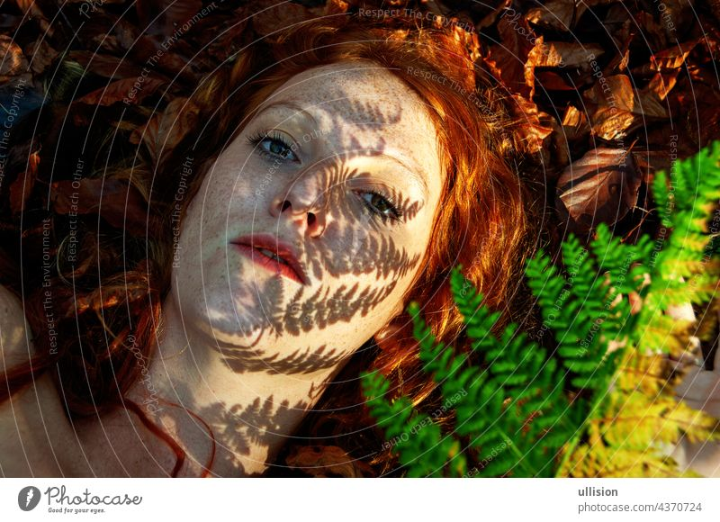 lovely portrait of a young seductive foxy girl in autumn, with shadow of fern frond on face, beautiful sexy attractive redhead woman forest ginger freckles