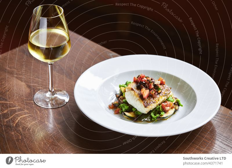 White wine and cod dish in restaurant white wine fish meal hospitality food drink still life indoors day dine eat table modern contemporary luxury gourmet
