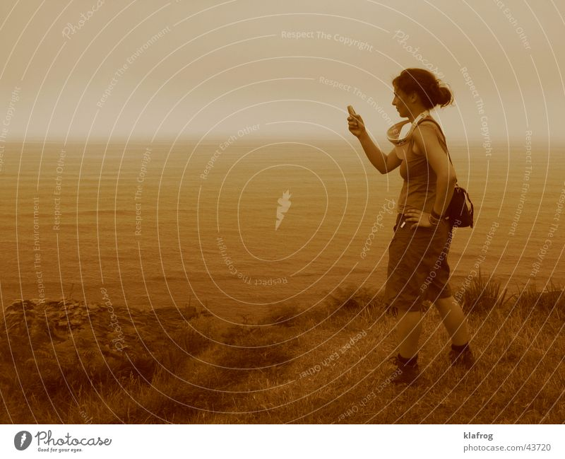 Woman Ocean Beach Calm Meadow Coast Telephone Empty Cellphone To hold on Mobility Photographer Take a photo Sepia Cliff Snapshot