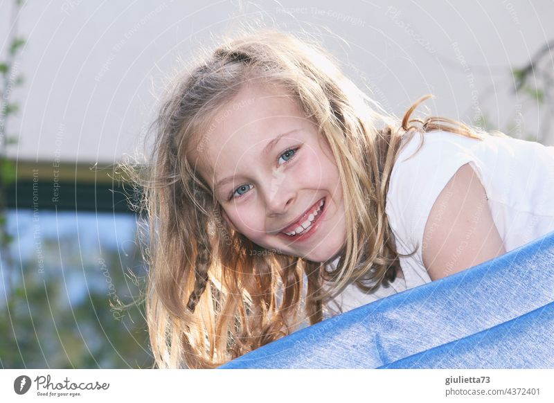 Portrait of a happy, laughing 8 year old girl with long blond hair playing on the slide Child Girl 1 Infancy Human being 8 - 13 years Summer Blonde Long-haired