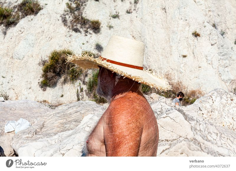 senior man in the beach with hat, nude torso vacation happy sea retirement holiday caucasian retired people sand leisure lifestyle summer ocean mature old