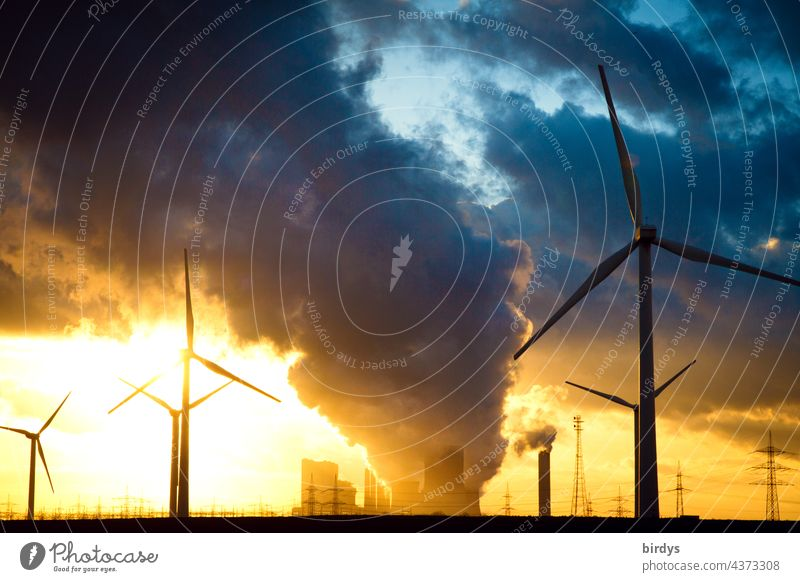 Wind turbines in front of a lignite-fired power plant at sunset in the backlight. Wind turbines Lignite power plant CO2 emission Climate change Air pollution