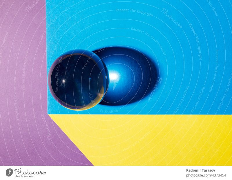 big glass ball on the table multicolored shadow reflection light circle colorful yellow sphere symmetrical games globe closeup playing orbs transparent bubble