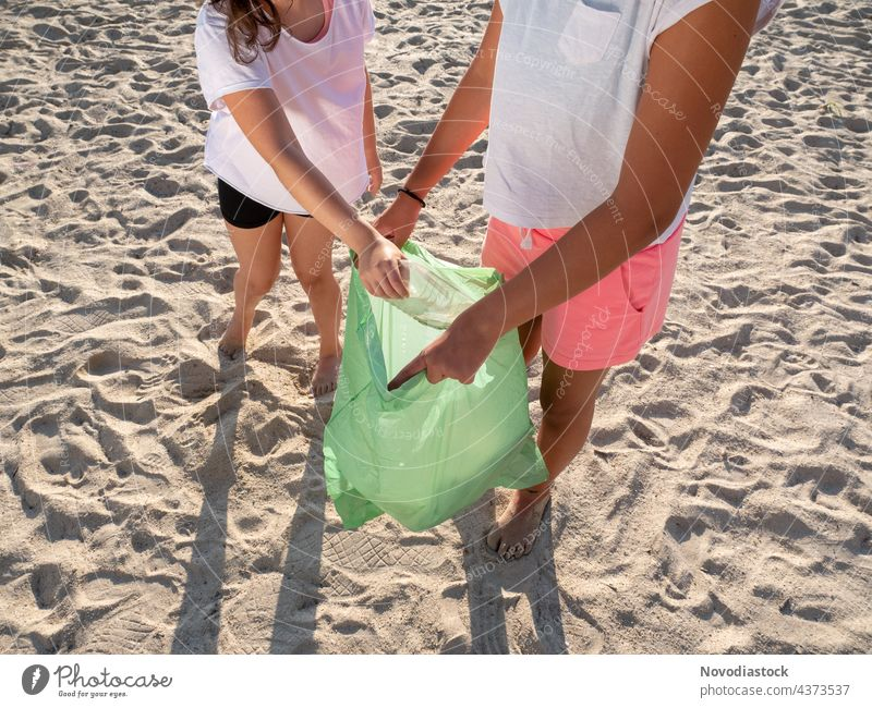 two girls collecting plastic on the beach, no faces shown environmental bag picking pecking people ecology male volunteer garbage rubbish rubber hand man human