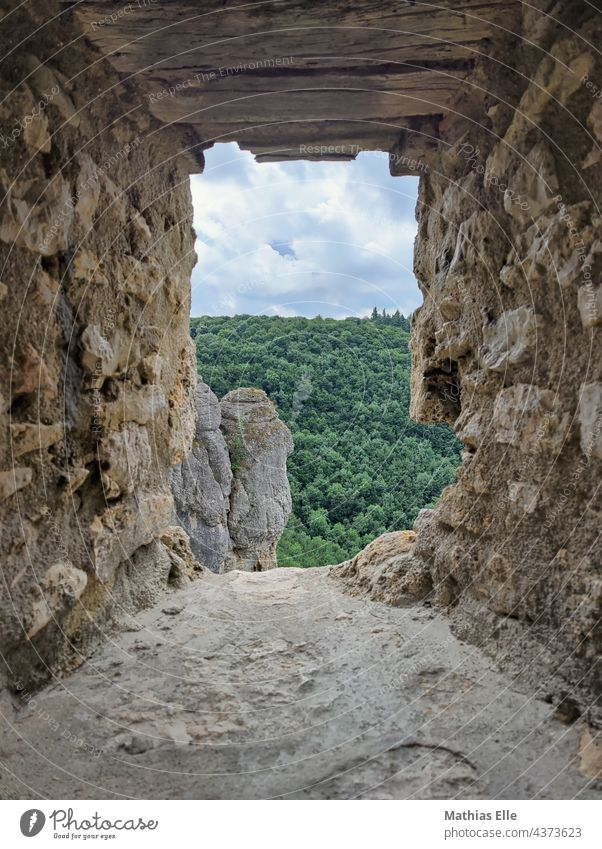 The view through an embrasure with rocks with forest in the background Summer Sand Sky Stone Exterior shot Colour photo Castle ruin Old times