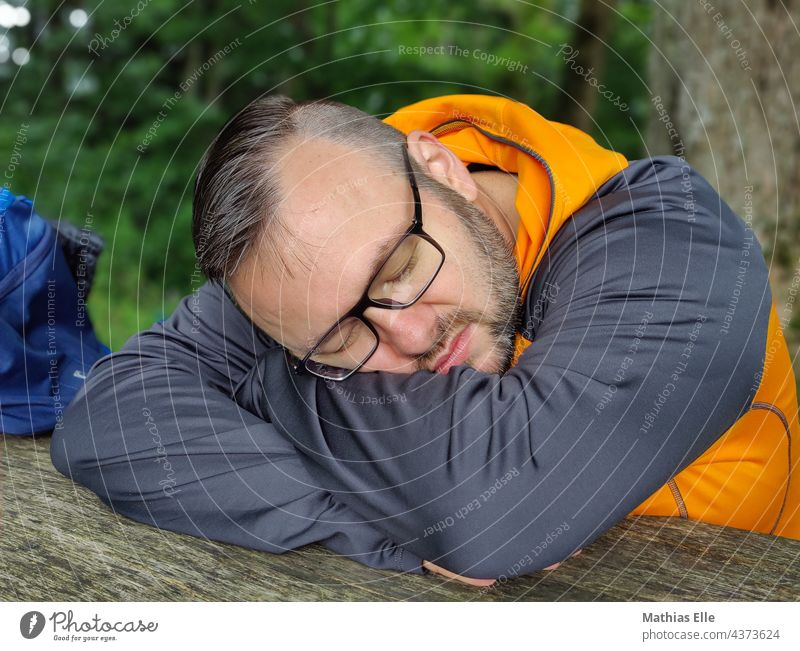Man with glasses sleeps and rests Lie Sleep Relaxation Summer Vacation & Travel done daypack Backpack Bag sleep late travel attracted Break tired Completed
