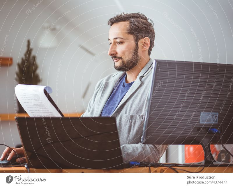 A man in the room is studying the documents. A man in casual clothes at a laptop. Work remotely business computer businessman casual clothing communication
