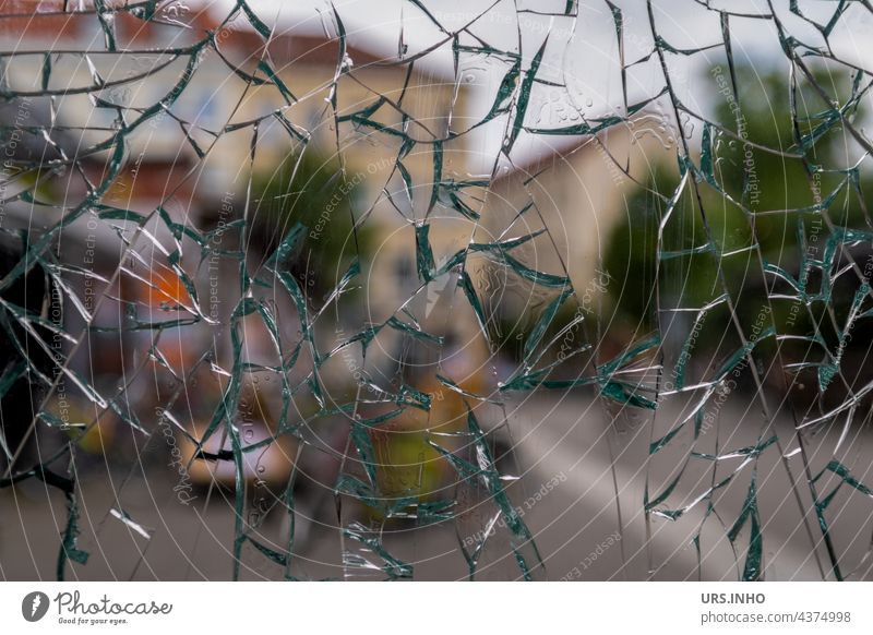through the heavily shattered glass window pane you can still see the houses in the background Slice Window Window pane Glass Pane Transparent Exterior shot