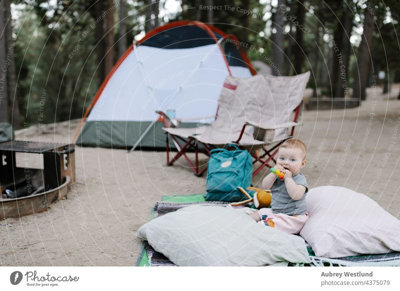 baby playing on the ground at a tent campsite 6 months california camper camping chair chewing child childhood daughter eating family fire forest fun girl happy