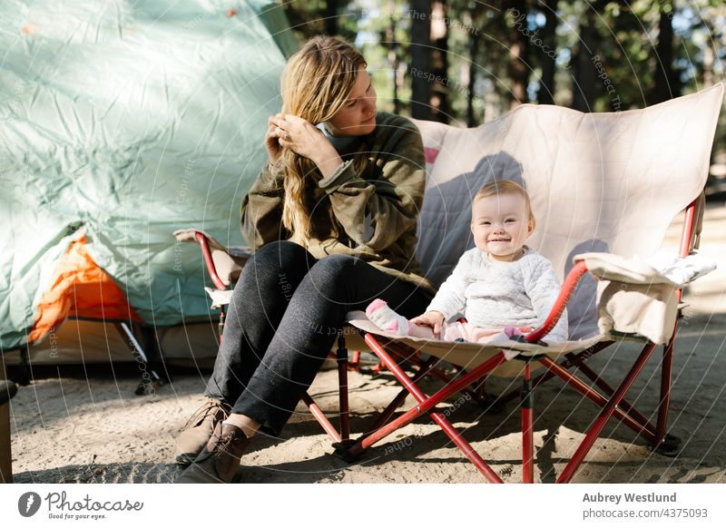 mother and her baby girl sitting on a camp chair outdoors while camping blonde california camp stove camper campsite caucasian child childhood cooking daughter
