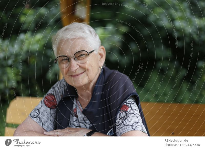 Senior woman sits at the edge of the forest and smiles 60 years and older portrait Female senior Woman Grandmother White-haired Gray-haired naturally Authentic
