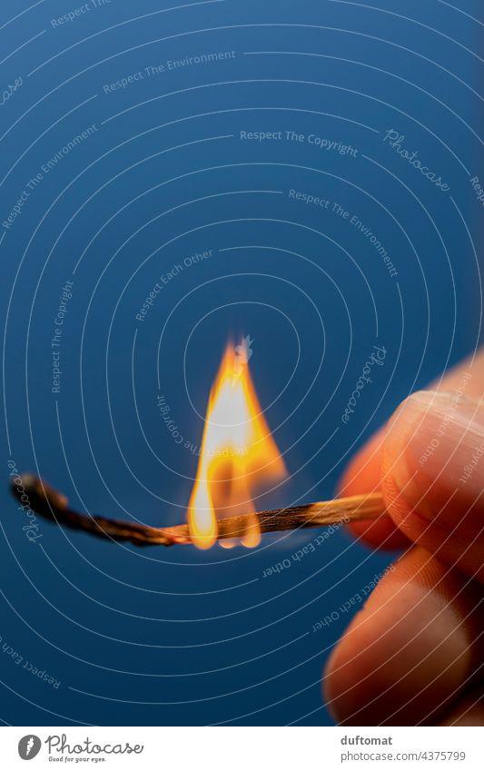 fingers hold burning match against blue background kindling Fire Burn cauterizing Match Flame Kindle Ignite Hot Dangerous Blaze Wood match head Warmth Physics