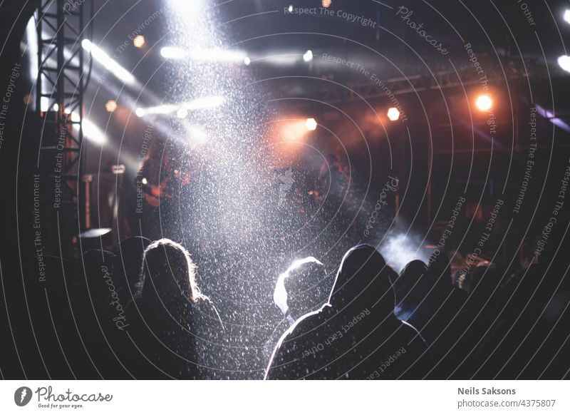 people listening concert in festival, stage lights and heavy rain. Doomy athmosphere behind Stage Music Rock music Shows Guitar String Floodlight Microphone