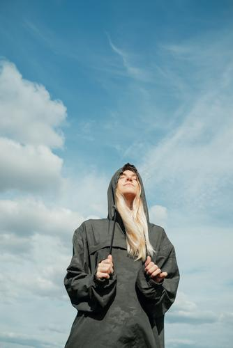 Young blond woman in khaki shirt with a hood standing in front of blue sky with her eyes closed pretty vertical landscape summer explorer freedom wind blonde