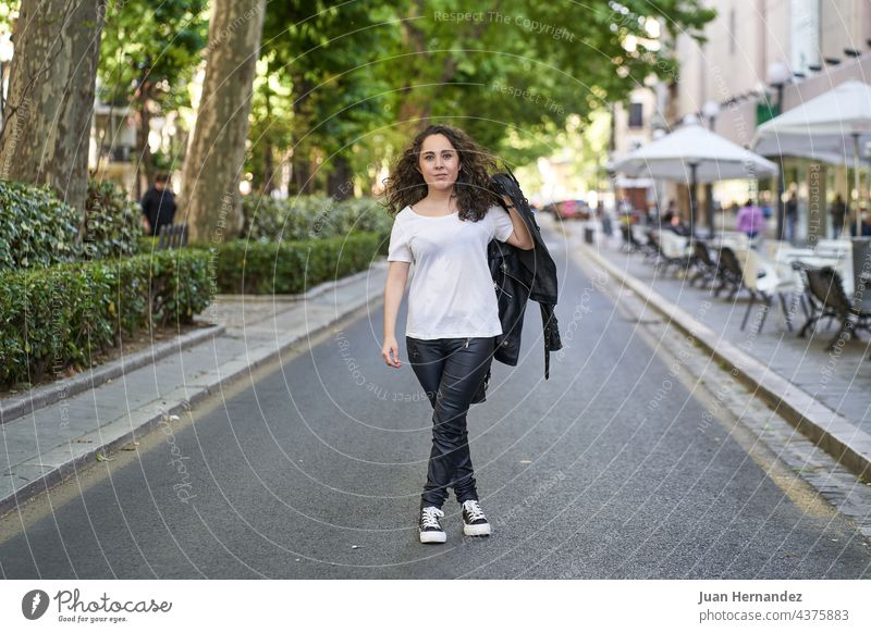 young woman dressed in black leather and white t-shirt in the middle of the road hispanic age 20s freedom happy happiness lady alone standing urban city street