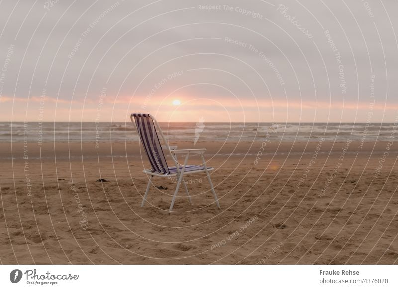 Blue and white folding chair on the beach at sunset Folding chair Beach White Striped sea view North Sea Ocean Camping chair on one's own forsake sb./sth.