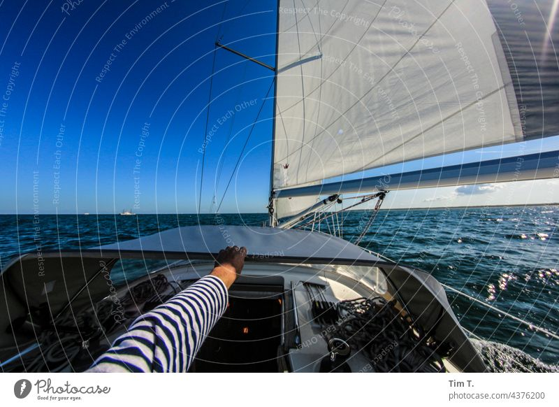 one hand holds on to the ship Sailor Seaman Hand arm Striped sweater Human being Sailing ship Watercraft Sailboat Navigation Sky Ocean Yacht Vacation & Travel