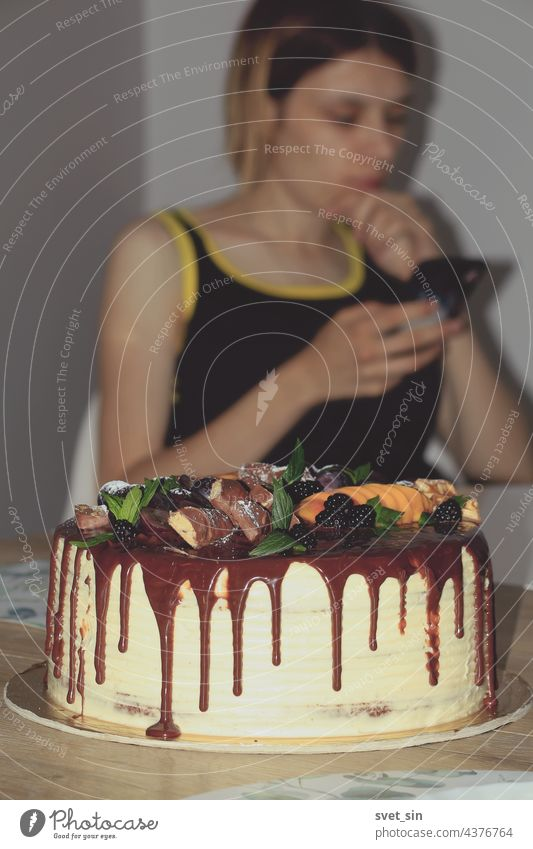 A birthday cake decorated with chocolate, berries, fruits, mint leaves, and a girl reading messages on a mobile phone in the background. Indoors. berry leaf
