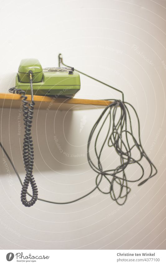 Here we have the salad | cable tangle and a green telephone on a wooden shelf in front of a white wall Cable Telephone cable dial telephone green phone Retro