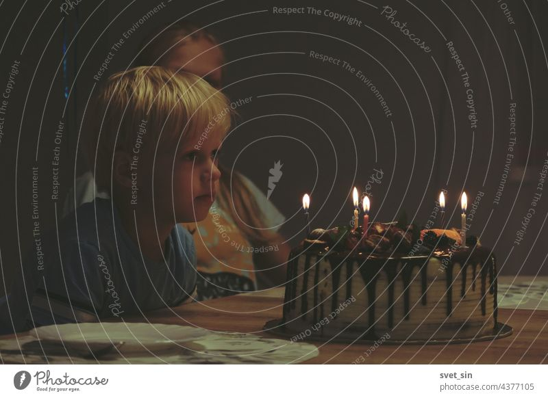 A blond boy is sitting at a table in a dark room and looking at a birthday cake with burning candles. Siblings are waiting for dessert at the birthday celebration.
