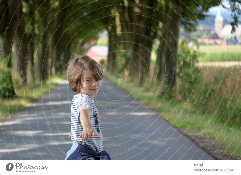 Boy stands on an avenue, looks and points to the photographer Human being Child Boy (child) Infancy Street Avenue Tree To go for a walk out In transit