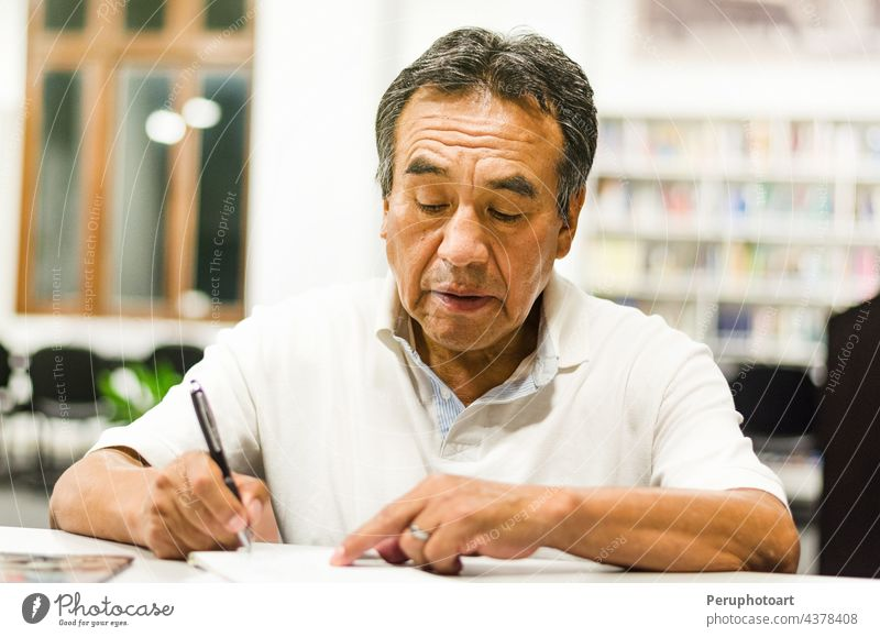 Serious senior man sitting on a library bench writing in his book. classroom education learning notes knowledge lifestyle people person research study studying