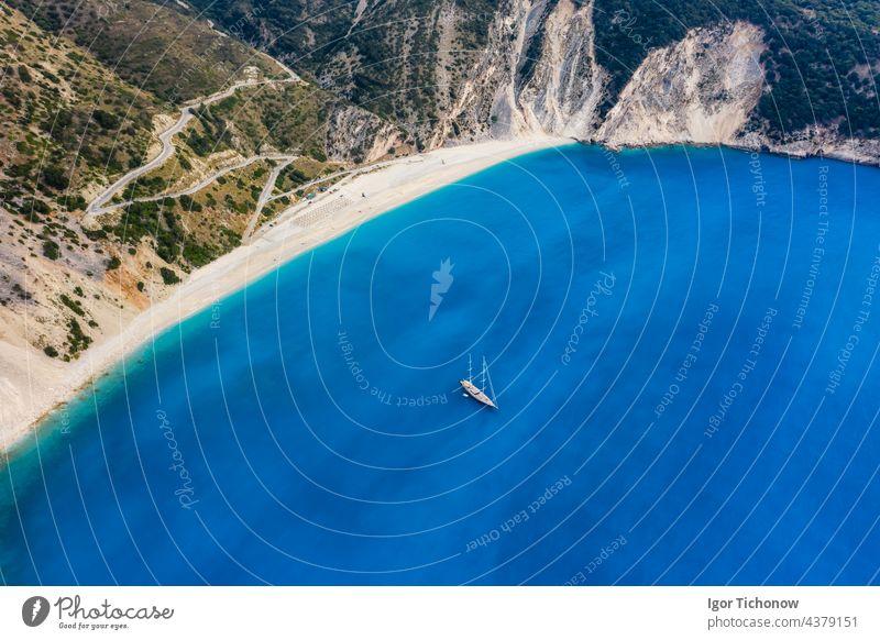 Aerial view of a luxury sailing yacht on the beach of Myrtos with blue bay on the island of Kefalonia, Greece myrtos Drone Beach Ocean Antenna Yacht Luxury