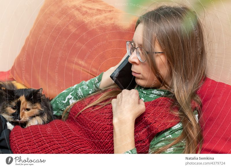 Serious brooding young woman talking with smartphone in her hands sitting on couch with her pet cat at home. young girl online communication wellness slow life