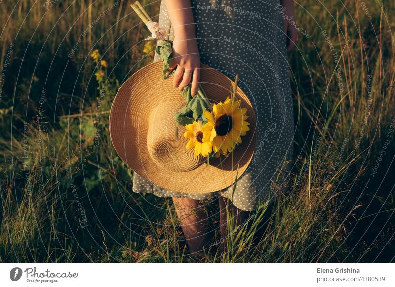 The girl holds a hat and a bouquet of sunflowers in her hands. summer grass field sunset slowdown silence closeness to nature natural seclusion self-discovery