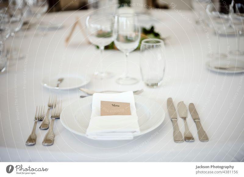 Table setting in a fancy restaurant table plate glass wedding posh clean formal menu utensil dinnerware stylish shiny elegance catering wineglass tableware