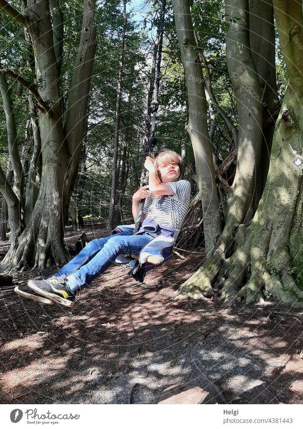 Child swinging on a tree swing in the forest Human being Schoolchild Forest Swing To swing Tree Beech wood Joy fun pleasure Light Shadow Sunlight Summer Nature