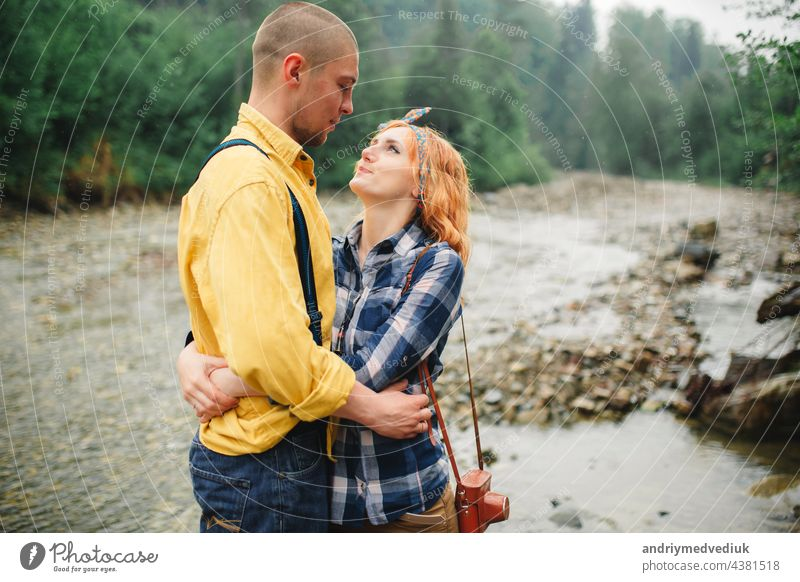Playful happy handsome couple having while walking in woods. tourists in the mountains. Adventure in nature concept. active relationship love playful piggyback