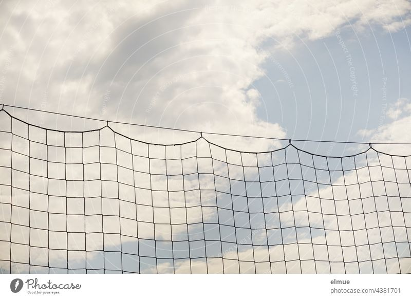ball catching net on a steel cable in front of light blue sky with clouds / hang out / football / network Ball catching net safety net Net Safety Clouds Network