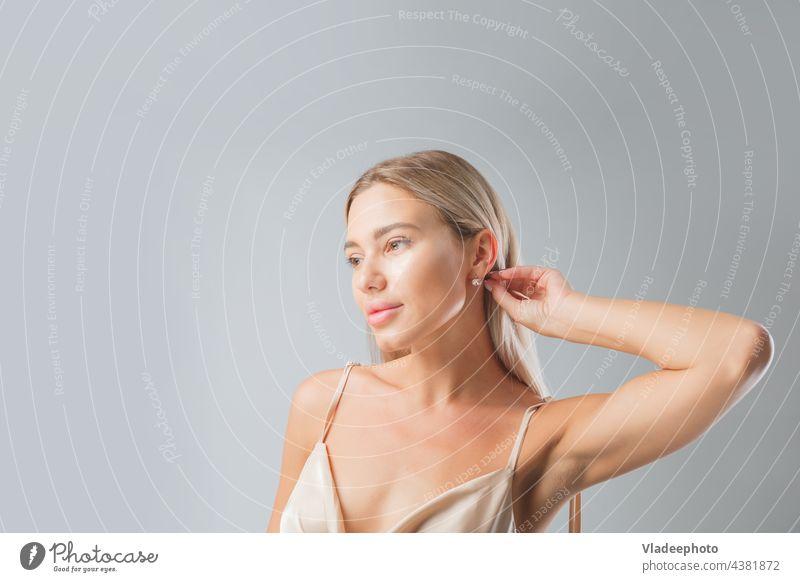 Beautiful blonde woman face close up portrait young studio on gray beauty earring jewelry lips silk nightie health linen skin care beautiful clean healthy hair