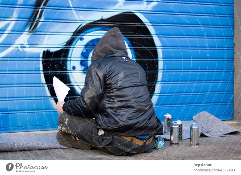 Artists painting a graffito Alternatively art artist blue b-boy band aerosol spray hood city color culture young youth graffiti hip-hop illegal lifestyle male