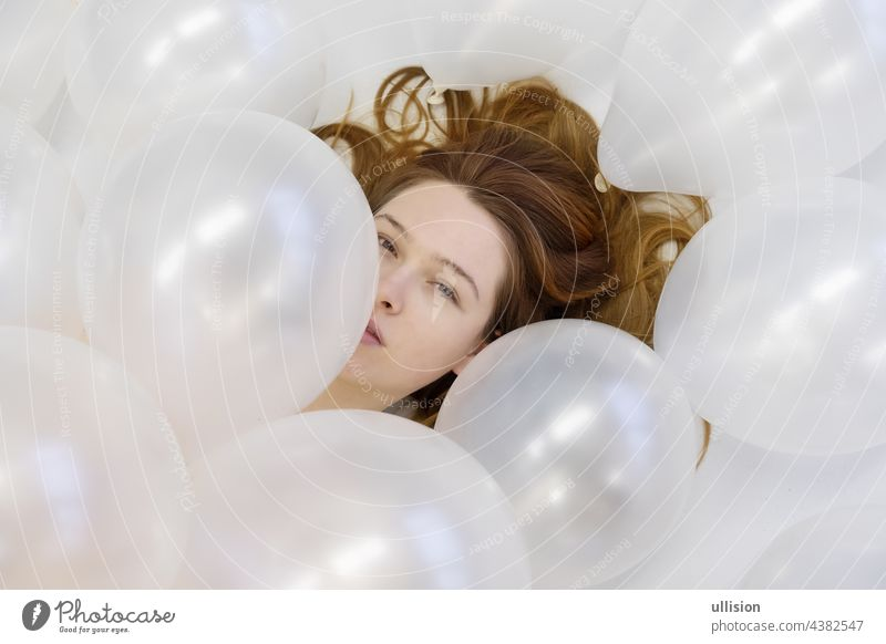 View from above beautiful young woman face between white iridescent balloons, beauty fashion concept. vogue redhead romantic bridal wedding love looking closeup
