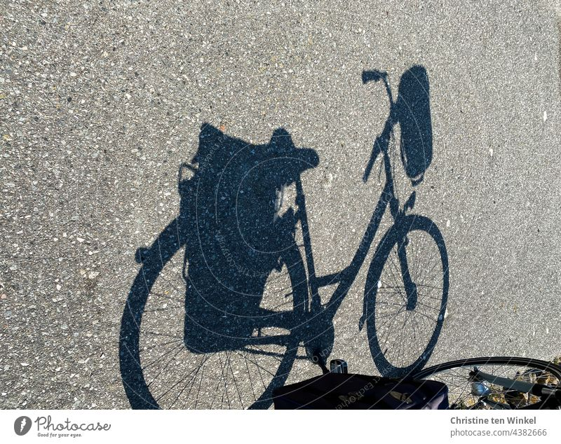 The shadow of a bicycle with saddlebags and handlebar basket Bicycle Shadow bicycle shadow panniers Handlebar basket Cycling Street Lanes & trails Asphalt