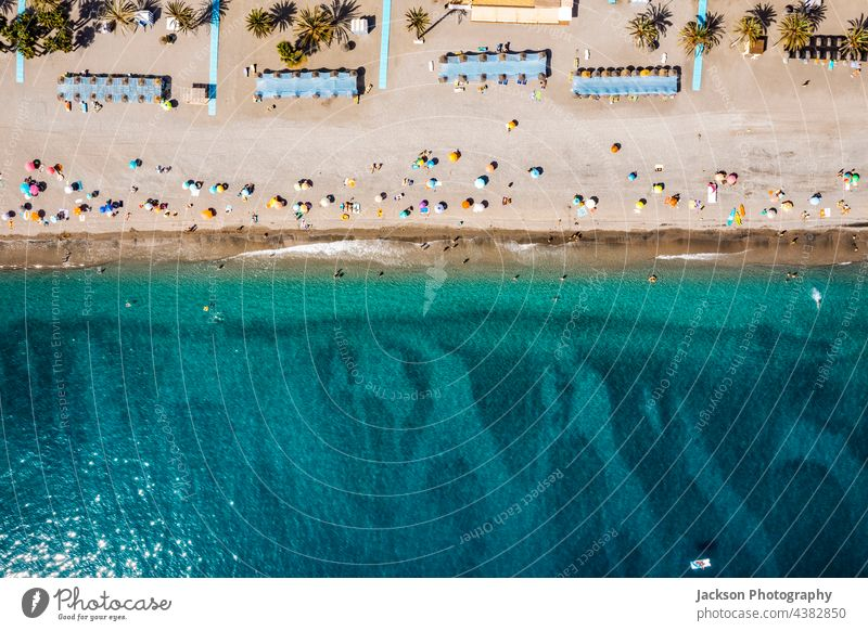 Aerial view of the sea and many people on the beach in Spain holidays costa del sol tree palm tree towel umbrellas leisure relax vacations concept copy space