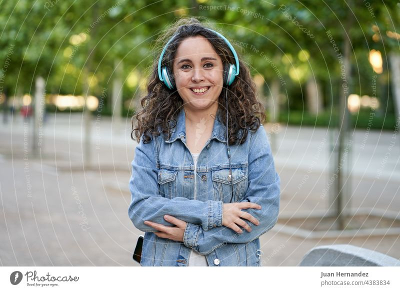 woman listens to music with her headphones connected to her smartphone young smart phone mobile phone cellular cellphone cell phone headset earphones listening