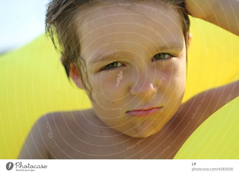 boy at the beach on a yellow background looking doubtful secret Contentment Mysterious youthful Uniqueness Change Identity Illusion naturally Gaze Conceited