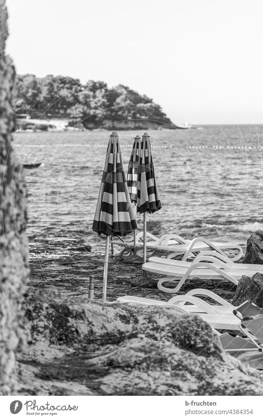closed umbrellas on the beach parasols Ocean Closed sun lounger Beach Rock Croatia Water Black & white photo Morning Bay on one's own Loneliness