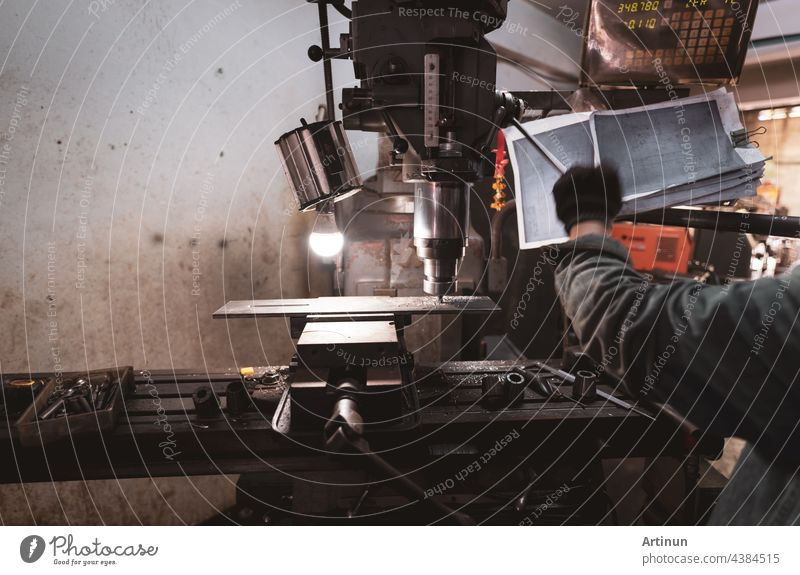 Milling machine working near worker with gloves. Tool for cut metal workpiece. Vertical milling machine with cemented carbide milling cutter. Steel manufacturing industry. Milling process. Metalwork.