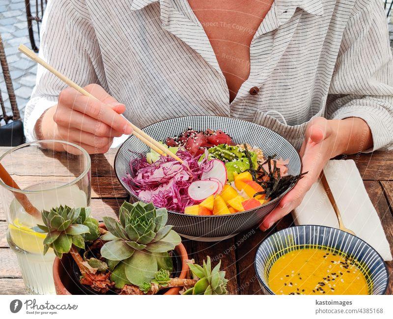Woman eating tasty colorful healthy natural organic vegetarian Hawaiian poke bowl using asian chopsticks on rustic wooden table. Healthy natural organic eating concept