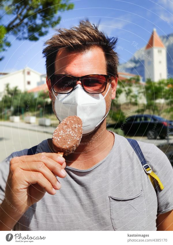 Young guy on summer vacations wearing corona virus protective face mask not beeing able to lick ice cream bar man portrait candy delicious sweet food enjoy