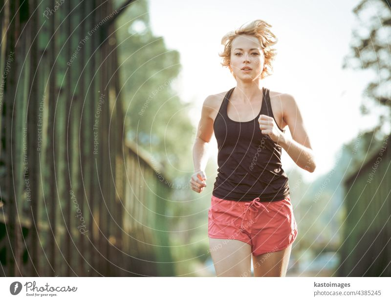 Athlete running on railaway bridge training for marathon and fitness. Healthy sporty caucasian woman exercising in urban environment before going to work. Active urban lifestyle