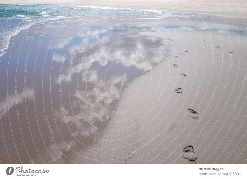 beach wet sand with fresh human bare footprints and blue cloud sky reflection and water waves seashore foot prints blue cloud sky reflection