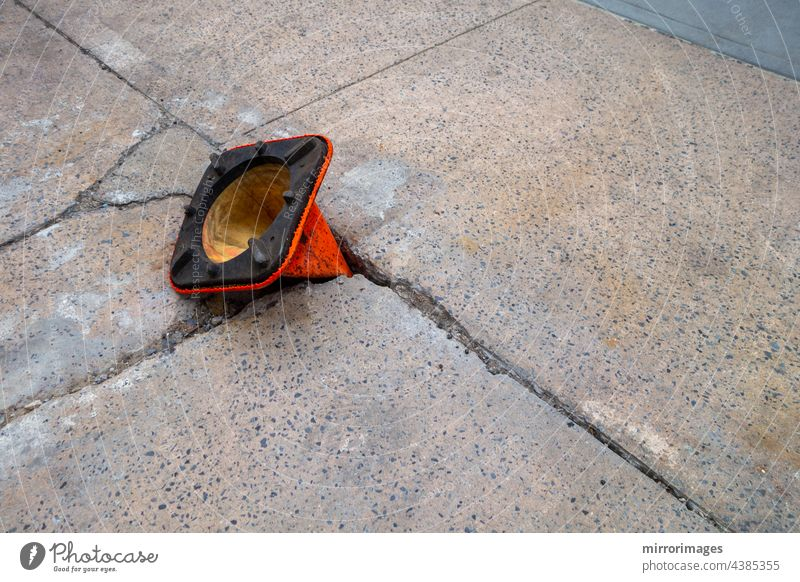 broken weathered sidewalk  with pot hole with orange cone upside-down in hole asphalt background black blue broken weathered street blacktop closeup concept