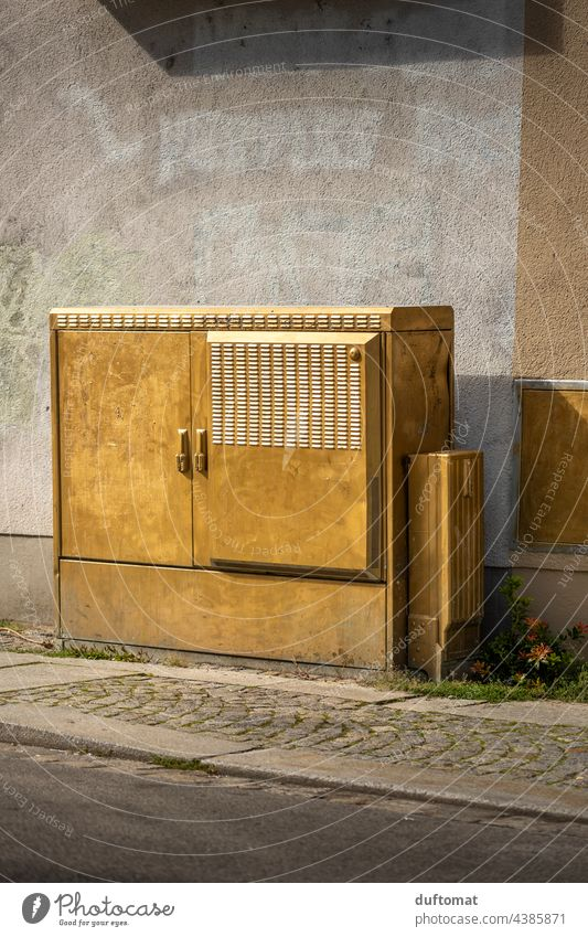 Power box in gold on house wall in Dresden-Neustadt Gold power box Wall (building) urban Joke wittily Exterior shot downtown Street off wayside Paving stone