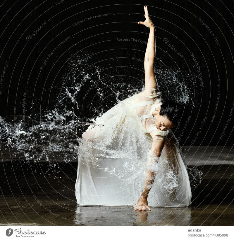 beautiful woman of Caucasian appearance with black hair dances in drops of water on a black background. The woman is wearing a white chiffon dress flexible aqua